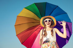 Teen girl with umbrella standing on the beach at the day time. Stock Photos