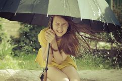 Teen girl under the big umbrella in a downpour Stock Images