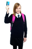 Teen girl in uniform holding up a cash card Royalty Free Stock Photos