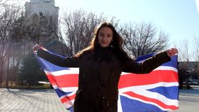 Teen girl with Union Jack waving by the wind and. Smiling full HD footage stock video footage