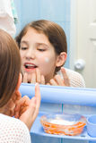 Teen girl use cosmetic cream royalty free stock photography