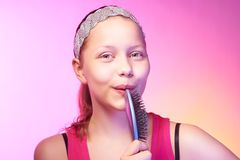 Teen girl uses hairbrush like a microphon Royalty Free Stock Photo