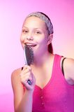 Teen girl uses hairbrush like a microphon Stock Photos