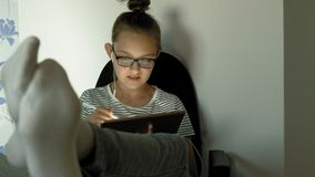 Teen girl uses tablet with headphones. Evening time stock video