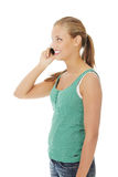 Teen girl using cell phone. Teen girl talking by cell phone. Isolated on white background Royalty Free Stock Photography