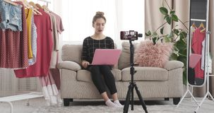 Teen girl using laptop and speaking about new outfit stock video footage