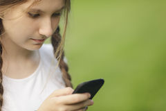 Teen girl using mobile phone. Outdoors in park Royalty Free Stock Photo