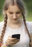 Teen girl using mobile phone. Outdoors in park Royalty Free Stock Photography