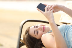Teen girl using a smart phone lying in a bench Stock Image