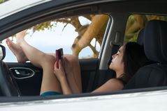 Teen girl using smartphone relaxing with legs out car window Royalty Free Stock Images