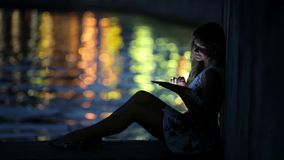 Teen girl using a tablet PC on the riverside stock video footage