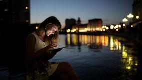 Teen girl using a tablet PC on the riverside. Of the city at evening time stock video