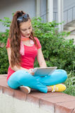 Teen girl using a tablet pc. Sitting outdoors Royalty Free Stock Images