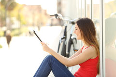 Teen girl using a tablet sitting in the street Stock Photography