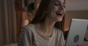 Teen girl video chatting using digital tablet at night