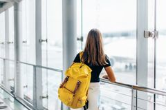 Teen girl waiting for international flight in airport departure terminal royalty free stock image