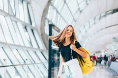 Teen girl waiting for international flight in airport departure terminal. Young passenger with backpack travelling on airplane. Teenager tourizm abroad alone stock photo