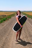 Teen Girl with Wake Board. A pretty teen girl on gravel road with wakeboard, no water in sight Stock Photography