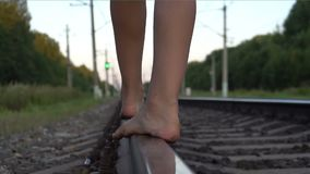 Teen girl walking barefoot along railroad rail. Slow motion shot of young girl`s bare feet close-up walking along railroad rail at summer evening stock video footage