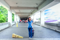 Teen girl walking with luggage at airport terminal Stock Image