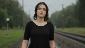 Teen girl is walking in the rain stock footage