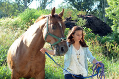 A teen girl walks with her horse. A teenage girl walks in the woods with her brown horse Royalty Free Stock Photo