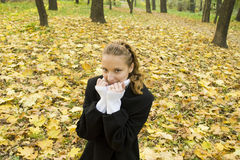 Teen girl warms herself in cold autumn park Stock Images