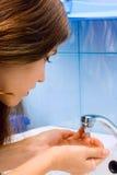 Teen girl wash hands. In bathroom Royalty Free Stock Photos