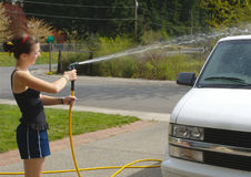Teen girl washes van with hose Stock Image