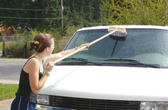 Teen girl washes van with scrub brush Royalty Free Stock Photo