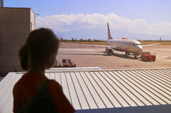 Teen girl watching at airport window Royalty Free Stock Image