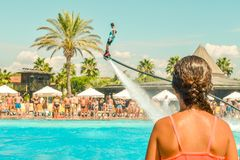 Teen girl watching fly board watershow at the pool. View from the back stock photography