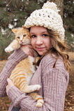 Teen girl wearing a crocheted hat holding a cat portrait Royalty Free Stock Image