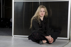 Teen girl wearing Gothic clothes sitting on the fl Stock Photography
