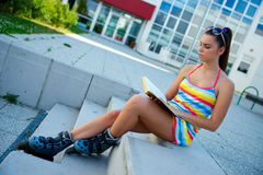 Teen girl wearing roller skates with book Royalty Free Stock Photography