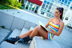 Teen girl wearing rollerskates with book Stock Photos