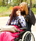 Teen girl on the wheelchair with her friend Stock Photo