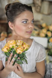Teen girl in a white dress. With a bouquet of yellow roses in  hands, photo in vintage style Stock Photo