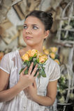 Teen girl in a white dress. With a bouquet of yellow roses in  hands, photo in vintage style Stock Photography