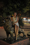 Teen girl in white dress next to the sculpture of a lion Royalty Free Stock Photos
