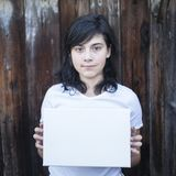 Teen girl with a white sheet in his hands. An old wooden wall on the background Stock Photography