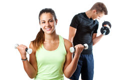 Teen girl working out with boy in background. Royalty Free Stock Photo
