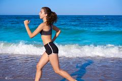 Teen girl workout running in beach shore royalty free stock image