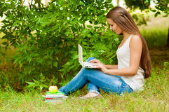 Teen girl works with the laptop on the grass Royalty Free Stock Photography