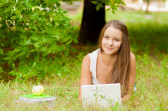 Teen girl works with the laptop on the grass Stock Photography