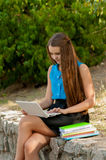 Teen girl works with the laptop in headphones and books Royalty Free Stock Photos