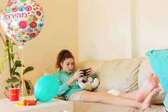 Teen girl with wounded knee. Teen girl with wounded and bandaged knee. Get well balloon Stock Photo