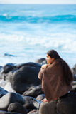 Teen girl wrapped in towel sitting on rocky beach Royalty Free Stock Photography