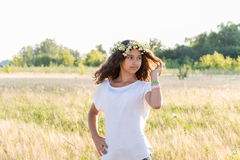 Teen girl with a wreath of daisies in  field Royalty Free Stock Photo