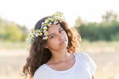 Teen girl with a wreath of daisies in  field Stock Images